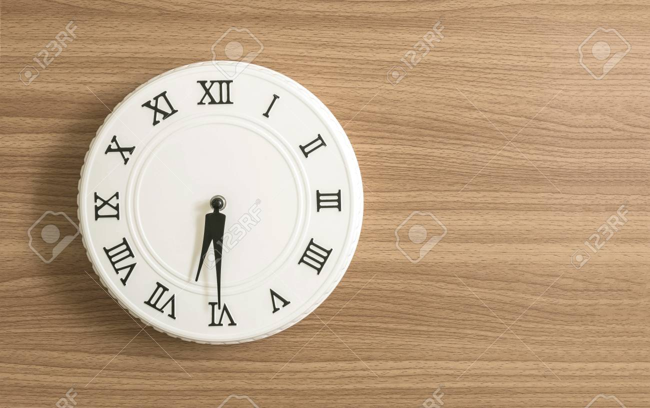 Closeup white clock for decorate show half past six or 6:30 a.m. on wood