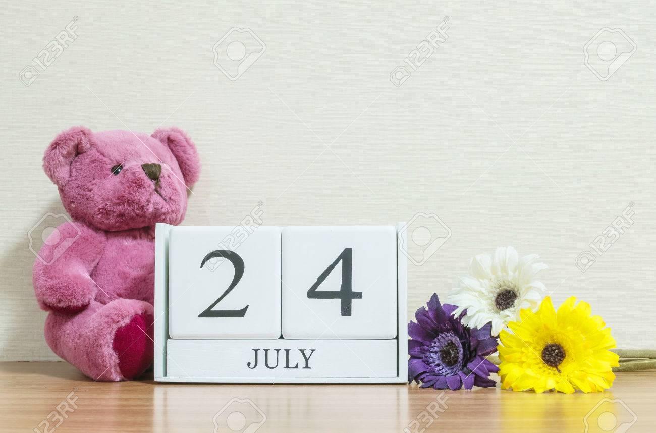クローズ アップ表面白い木製カレンダー 7 月 24 日単語黒茶色の木製の机と部屋でクリーム色の壁紙テクスチャ コピー スペース カレンダーで選択と集中を背景 の写真素材 画像素材 Image