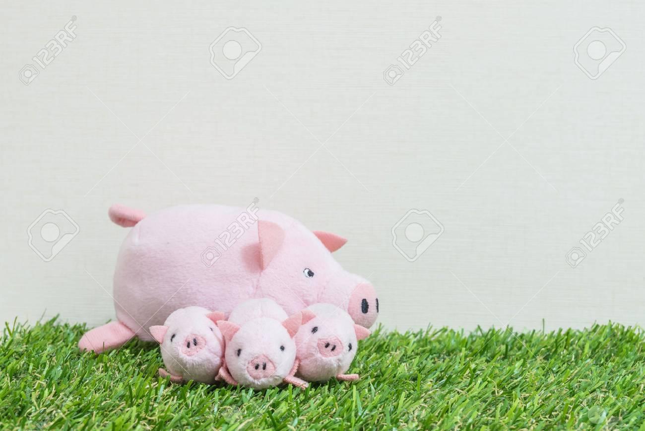 Poupee De Cochon Rose Closeup Mignon Et Trois Petit Cochon Sur L Herbe Artificielle Et Fond De Papier Peint Couleur Creme Mur Texture Avec Espace
