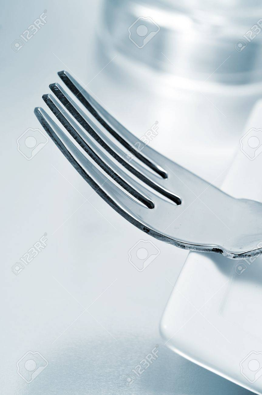 a dinner set formed by a plate, a fork and a glass Stock Photo - 8399638