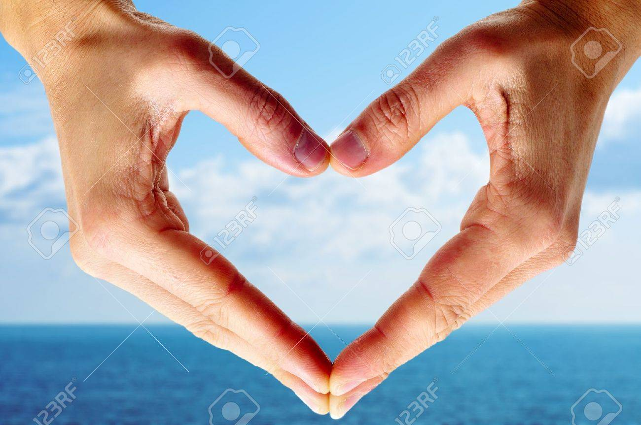 man hands forming a heart with the ocean and the sky in the background Stock Photo - 12553862