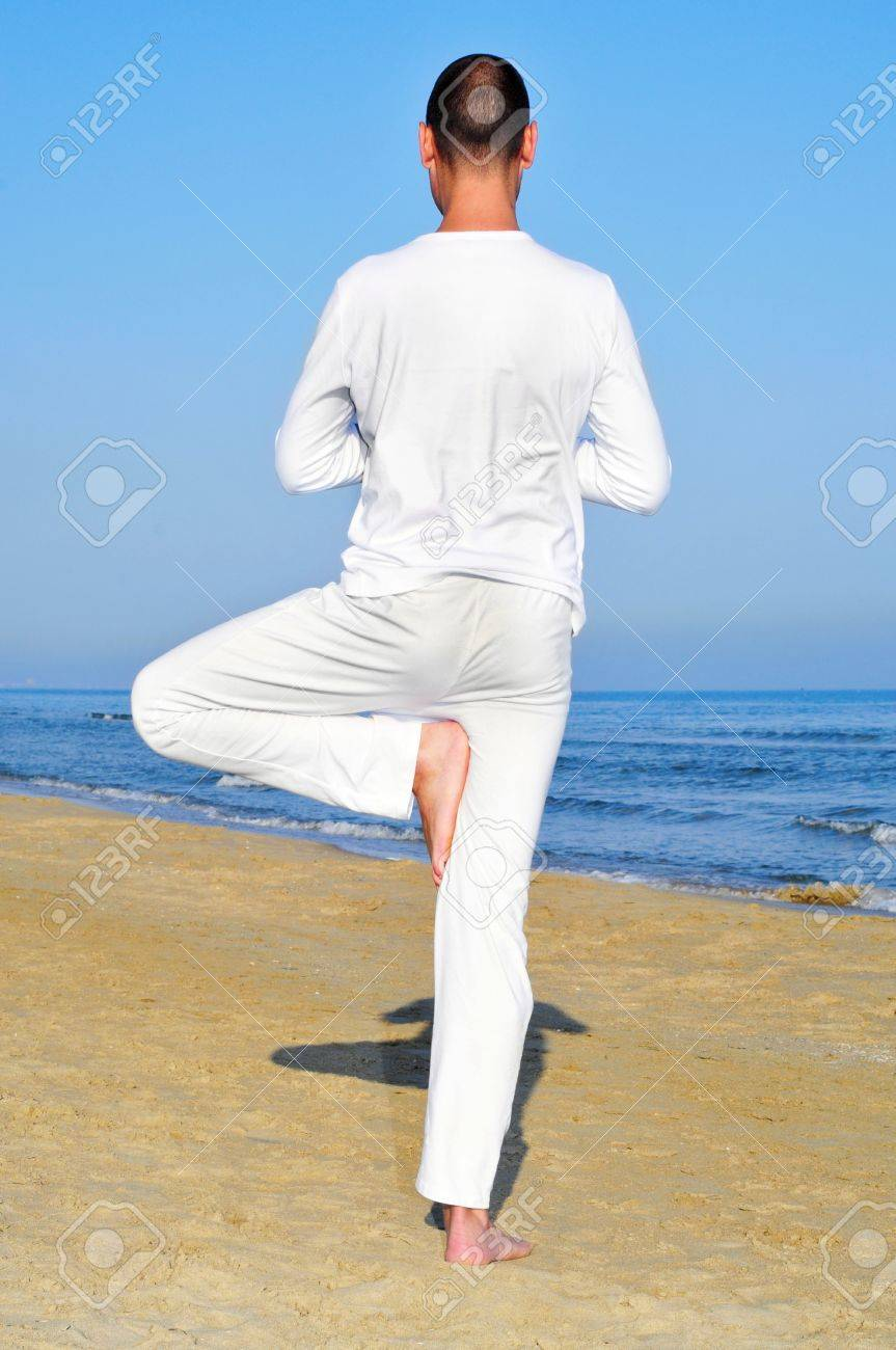 a yogi practicing the tree pose on the beach Stock Photo - 15424023