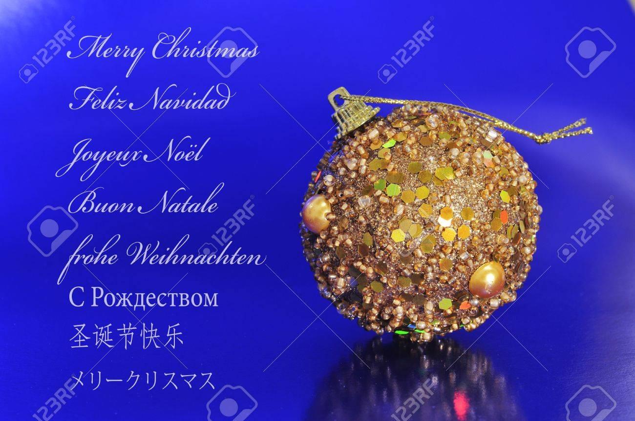 Una Bola De Oro De La Navidad En Un Fondo Azul Y La Frase Feliz Navidad Escrita En Inglés Español Francés Italiano Alemán Ruso Chino Y Japonés