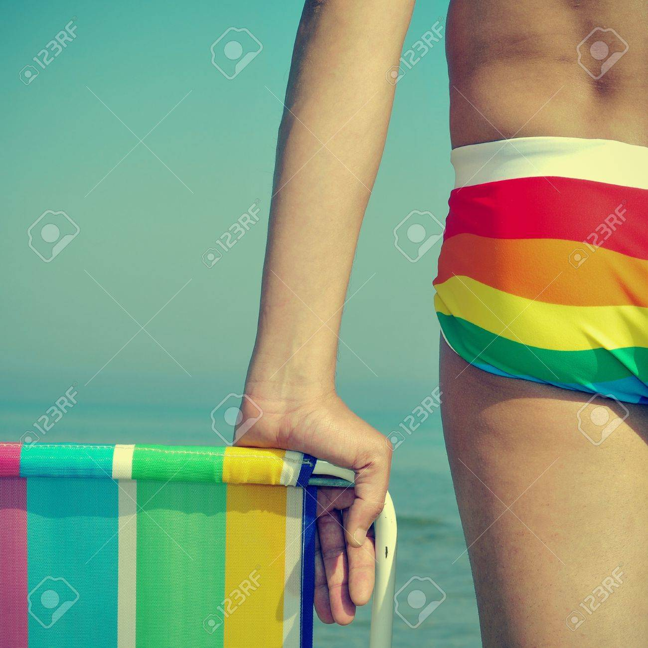 someone wearing a rainbow swimsuit and a colorful deck chair on the beach Stock Photo - 17794251