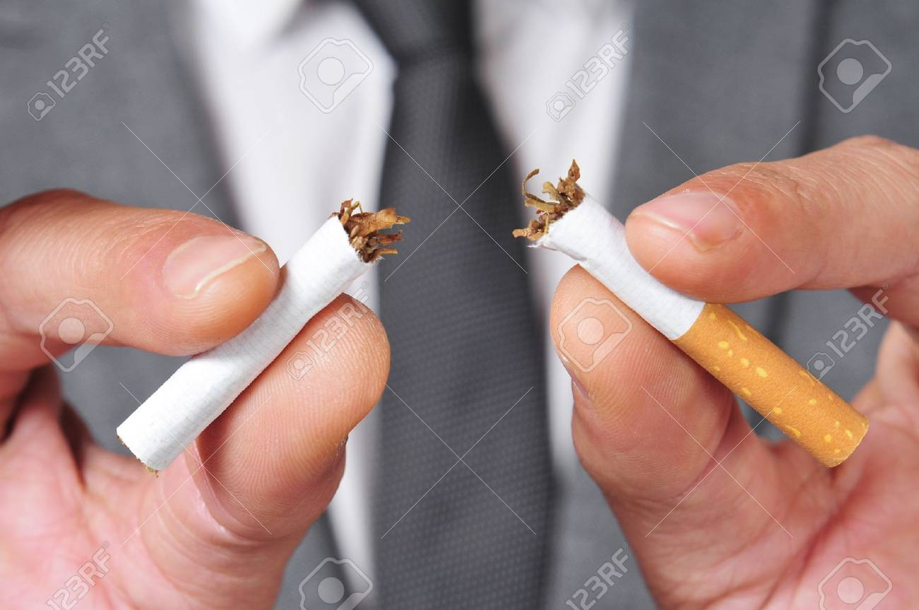 a man wearing a suit breaking a cigarette with his hands Stock Photo - 19529024