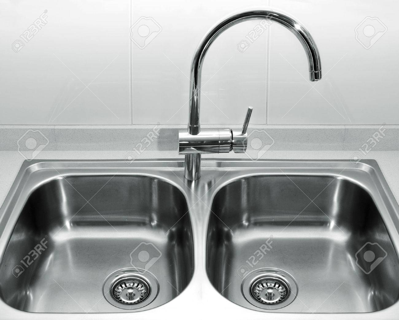 A Double Bowl Stainless Steel Kitchen Sink On A White Granite