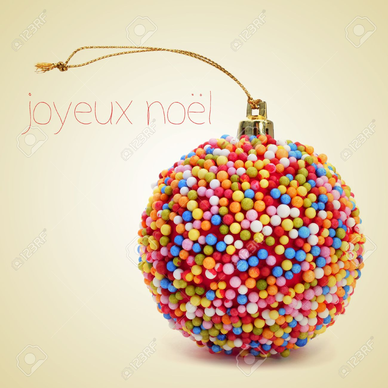 a christmas ball coated with nonpareils of different colors and the sentence joyeux noel merry
