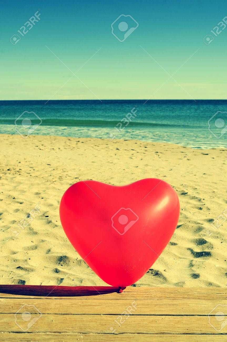 a red heart-shaped balloon on a beach, with a retro effect Stock Photo - 25614521