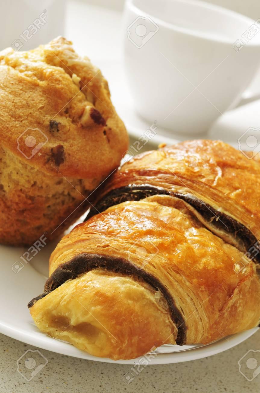 Foto Di Una Tavola Imbandita.Un Croissant Al Cioccolato E Un Muffin In Un Piatto Su Una Tavola Imbandita Con Una Tazza Di Caffe In Background