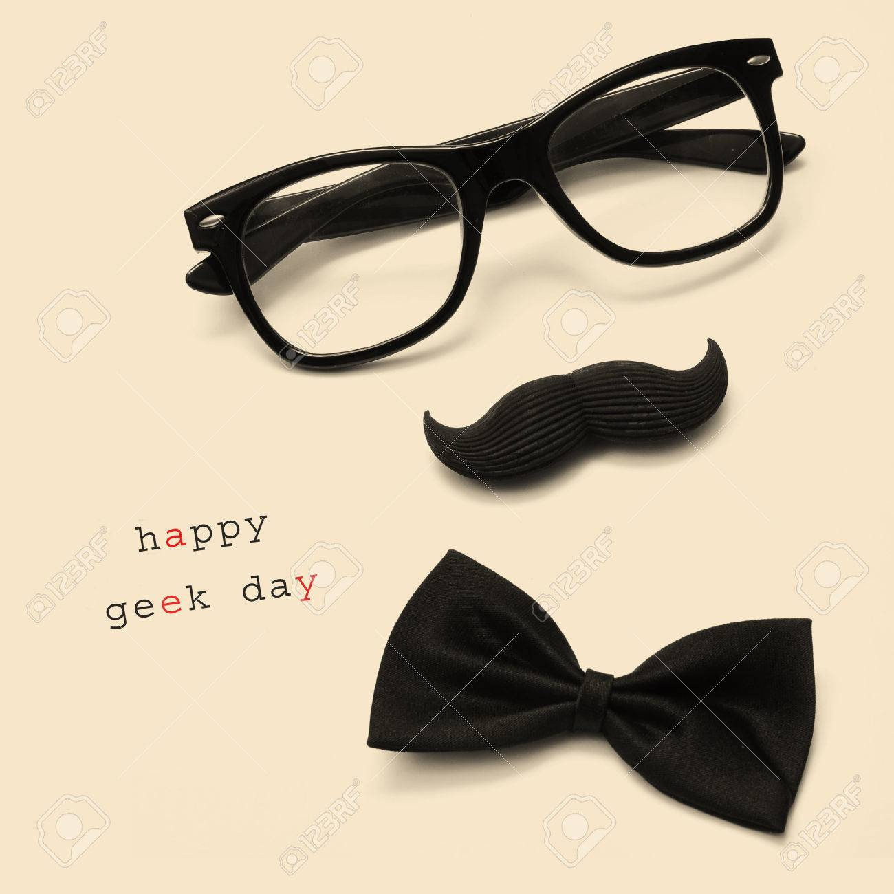 Stock Photo  A Pair Of Glasses, A Mustache, A Bow Tie And The Sentence  Happy Geek Day On A Beige Background