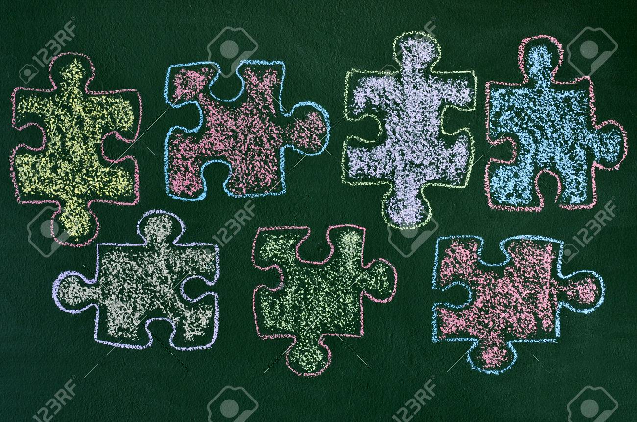 Some puzzle pieces drawn with chalk of different colors on a some puzzle pieces drawn with chalk of different colors on a green chalkboard as the biocorpaavc