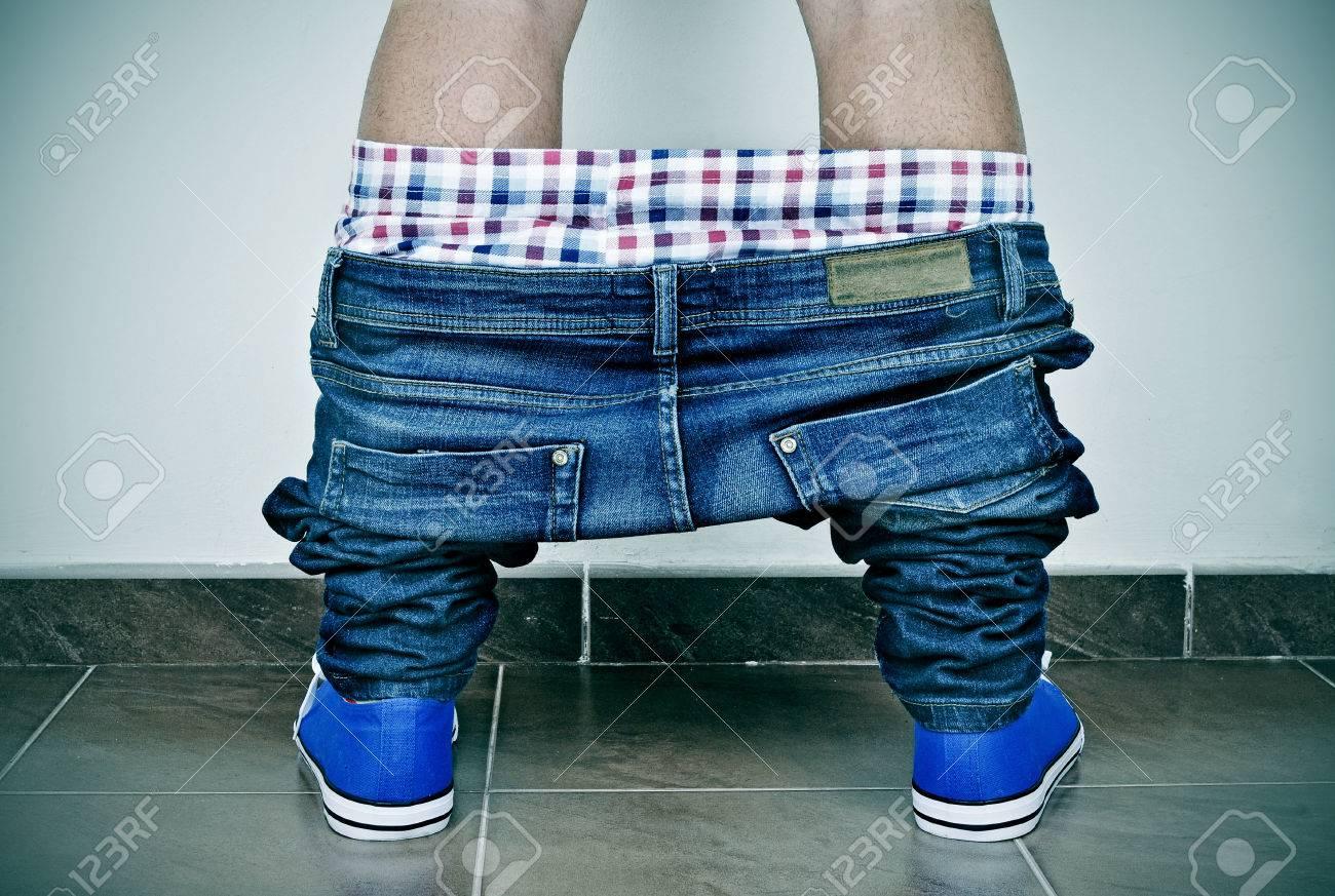 Primo piano di un giovane uomo caucasico con i pantaloni denim e le mutande giù, visto da dietro