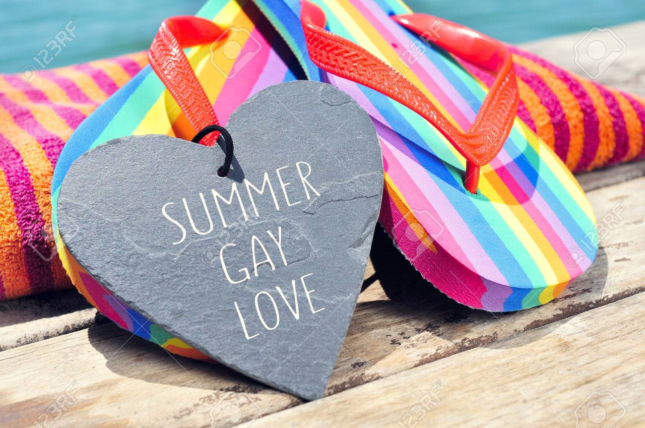 0144ef0ae4536 Stock Photo - the sentence summer gay love written in a heart-shaped slate  stone and a pair of rainbow flip-flops and a beach towel on a boardwalk  above the ...