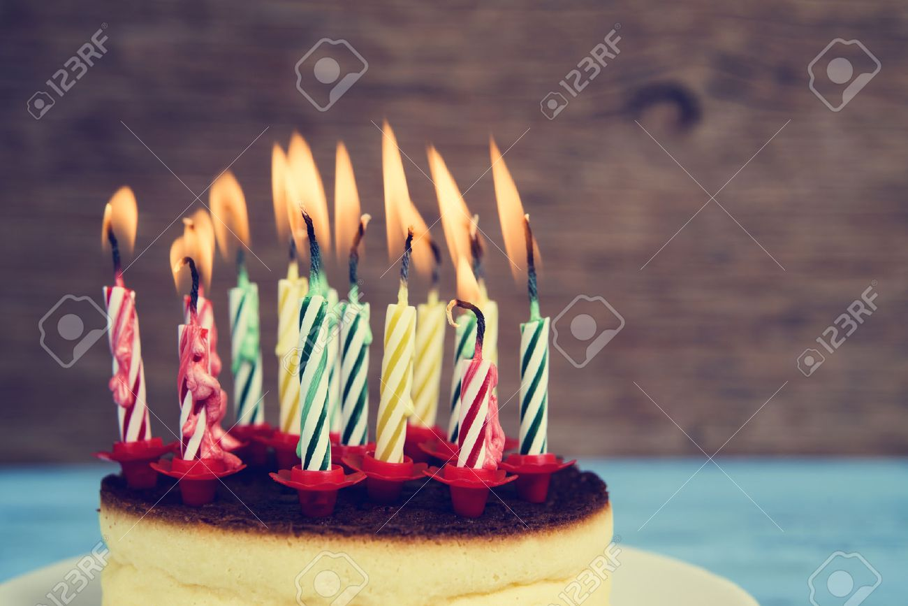 Closeup Of A Cheesecake With Some Lighted Birthday Candles Of