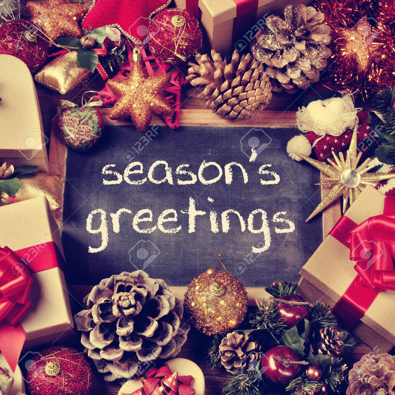 The text seasons greetings written in a chalkboard surrounded stock photo the text seasons greetings written in a chalkboard surrounded by some gifts and a pile of different christmas ornaments such as baubles m4hsunfo