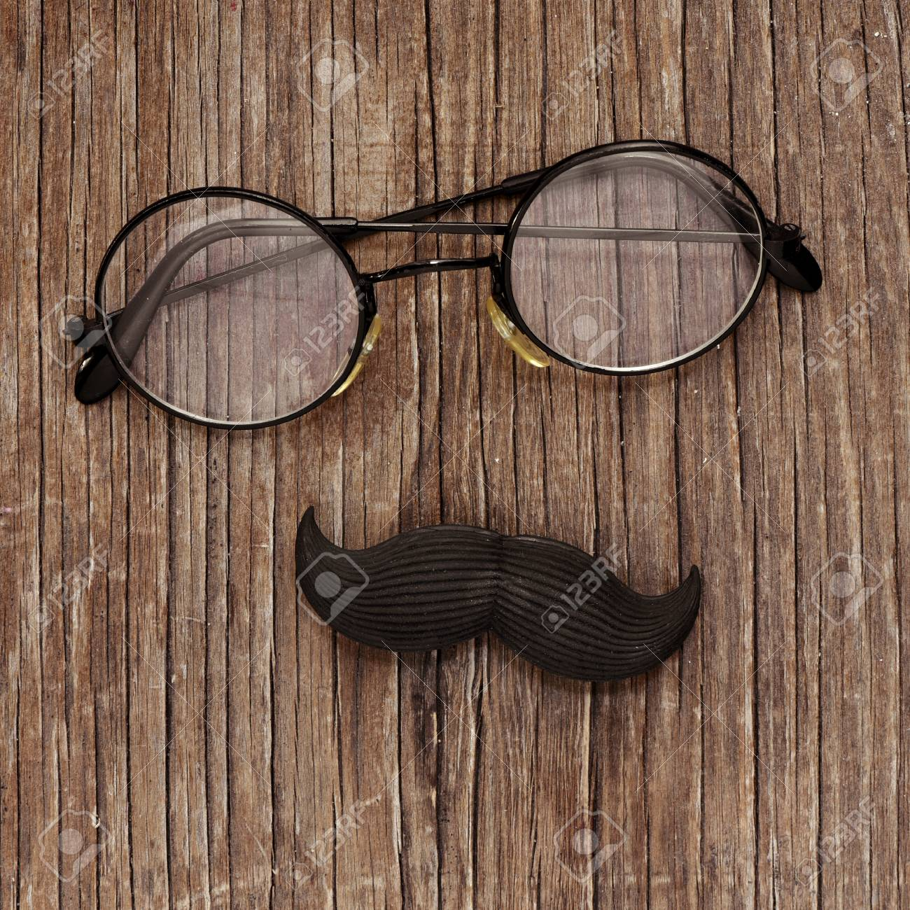 113cda34bb43ac Banque d images - Une paire de lunettes rondes-encadrée et une fausse  moustache sur une surface en bois rustique, représentant un visage de  l homme