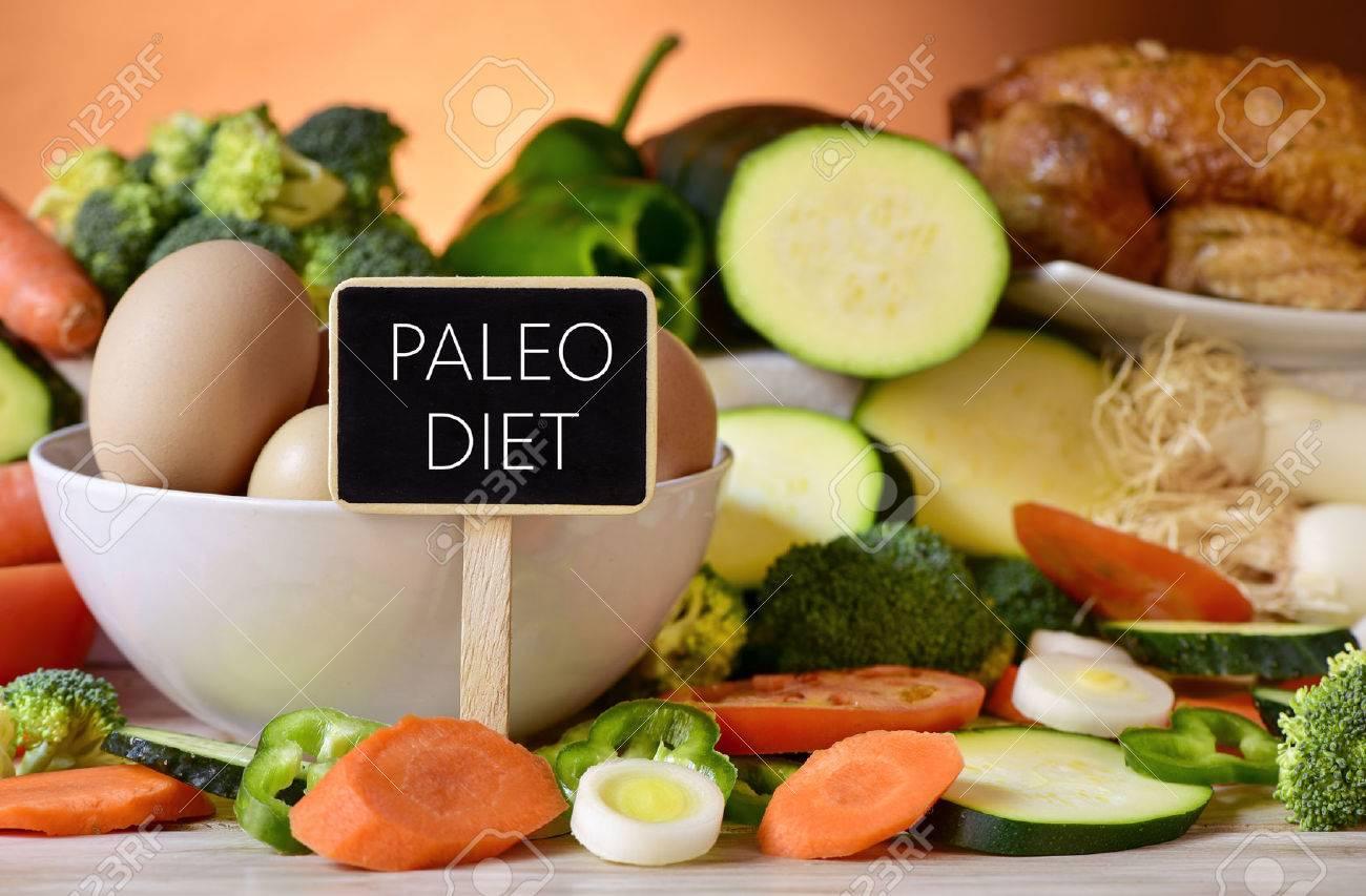 closeup d'un panneau avec le texte paleo sur une table pleine de légumes crus différents, un bol avec des ?ufs de poulet et un poulet Banque d'images - 48969308