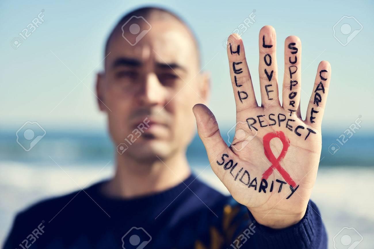 gros plan de la main d'un jeune homme de race blanche avec un ruban rouge pour la lutte contre le sida peinte en elle, et les mots aide, l'amour, le soutien, les soins, respect et de solidarité Banque d'images - 49098781