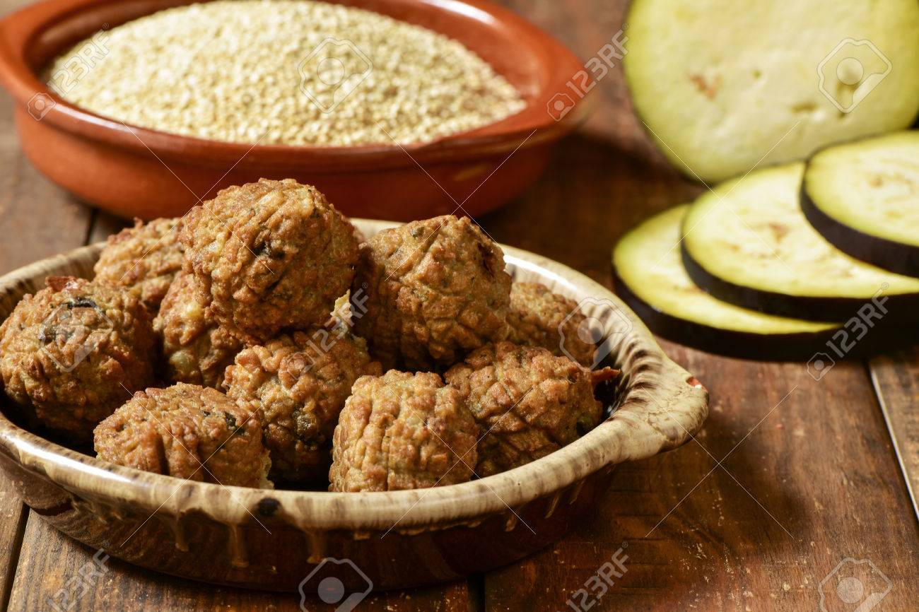 some vegan meatballs in an earthenware plate on a rustic wooden table, with some vegetables in the background - 49158887