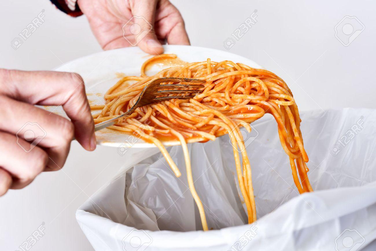 gros plan d'un jeune homme qui jette les restes d'un plat de spaghettis à la poubelle Banque d'images - 50252958