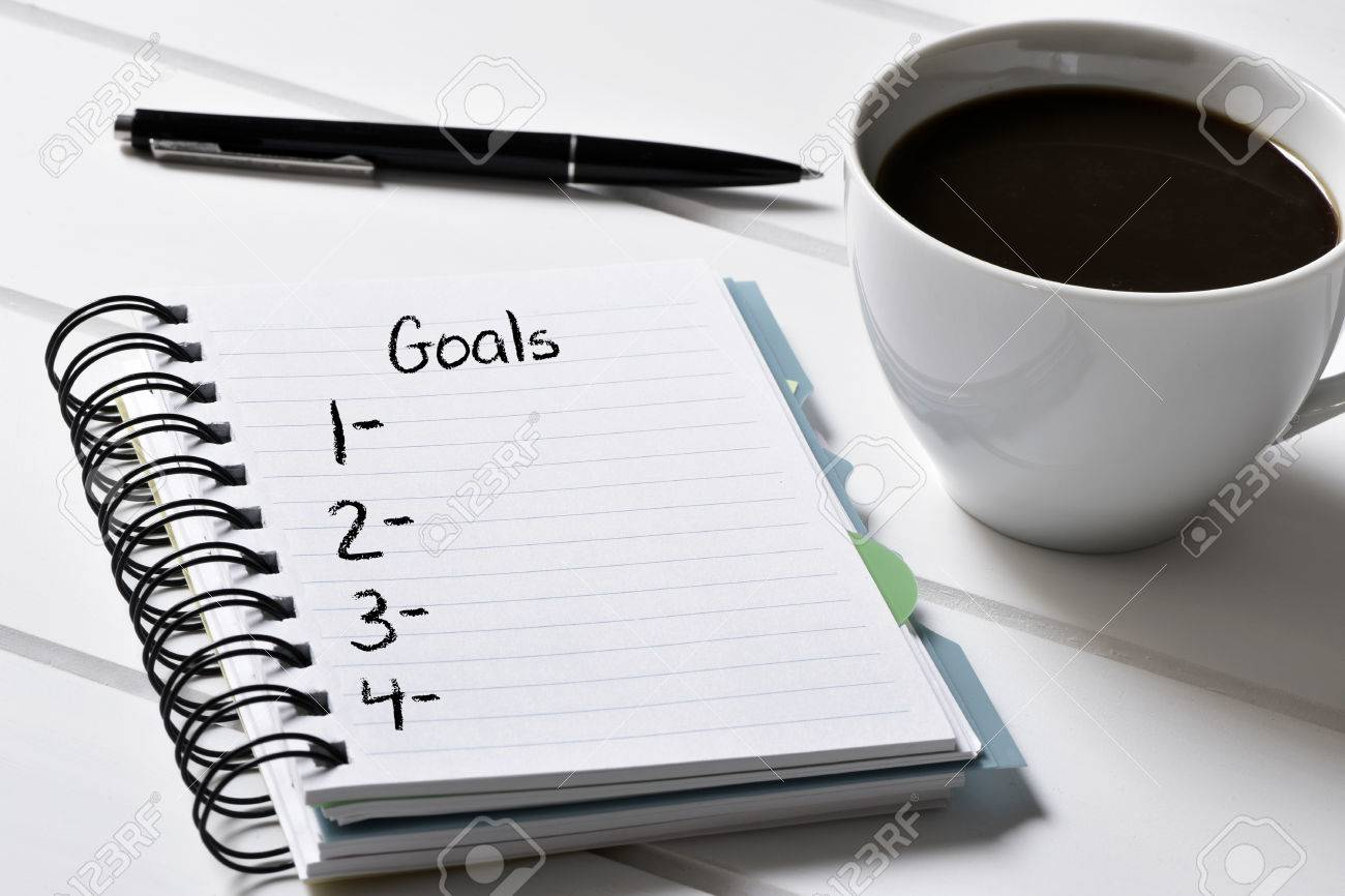 closeup of a notebook with a blank list of goals and a cup of coffee on a white wooden table - 51014827