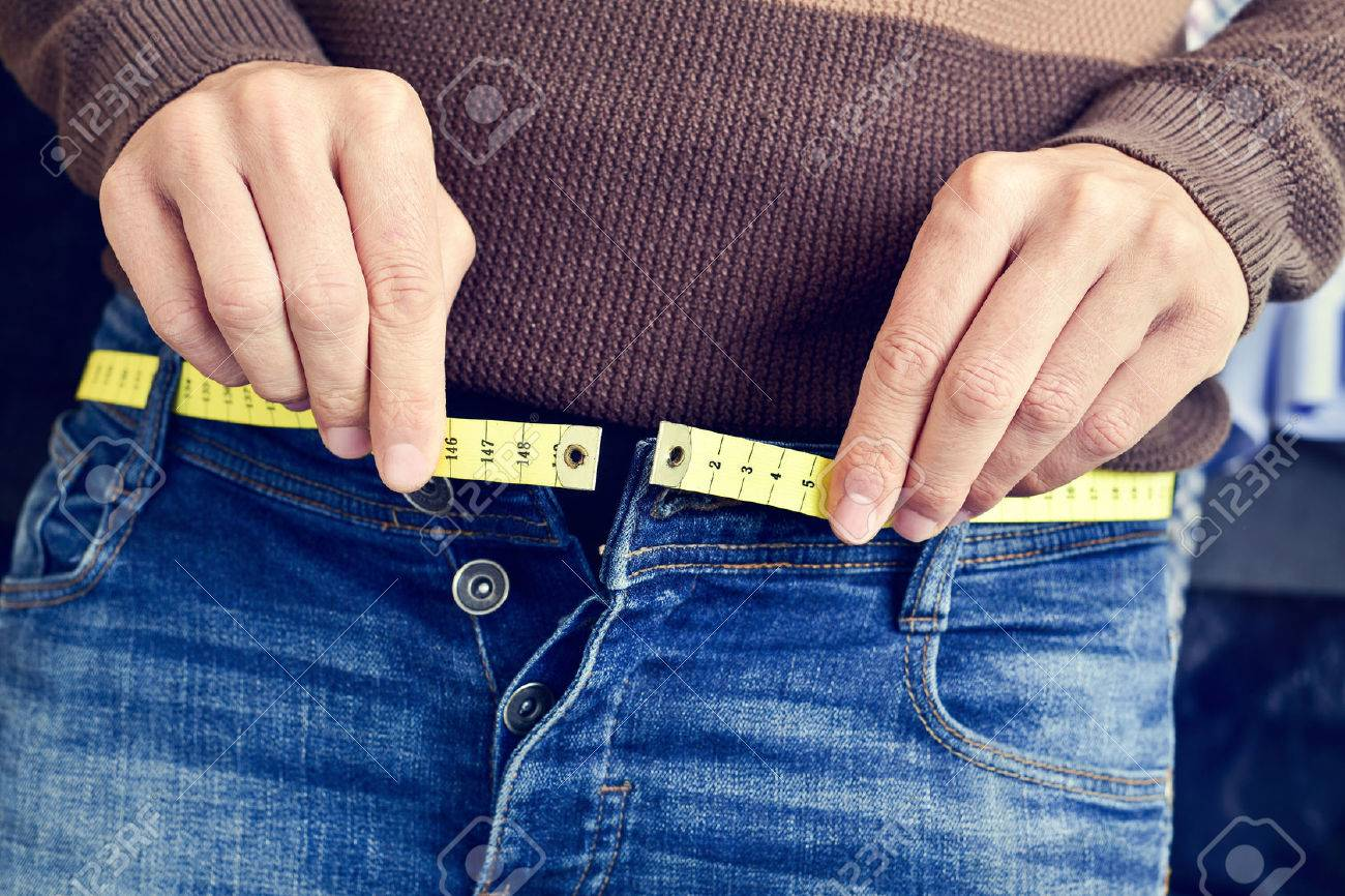 a young man with a measuring tape as a belt tries to fasten his trousers, because of the weight gain - 51874775