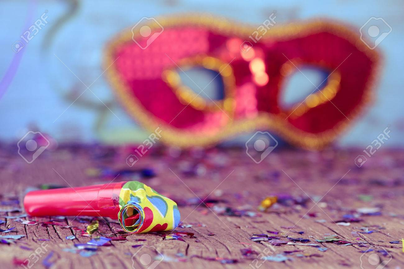closeup of a party horn on a rustic wooden surface full of confetti and an elegant red and golden carnival mask in the background Banque d'images - 51900578