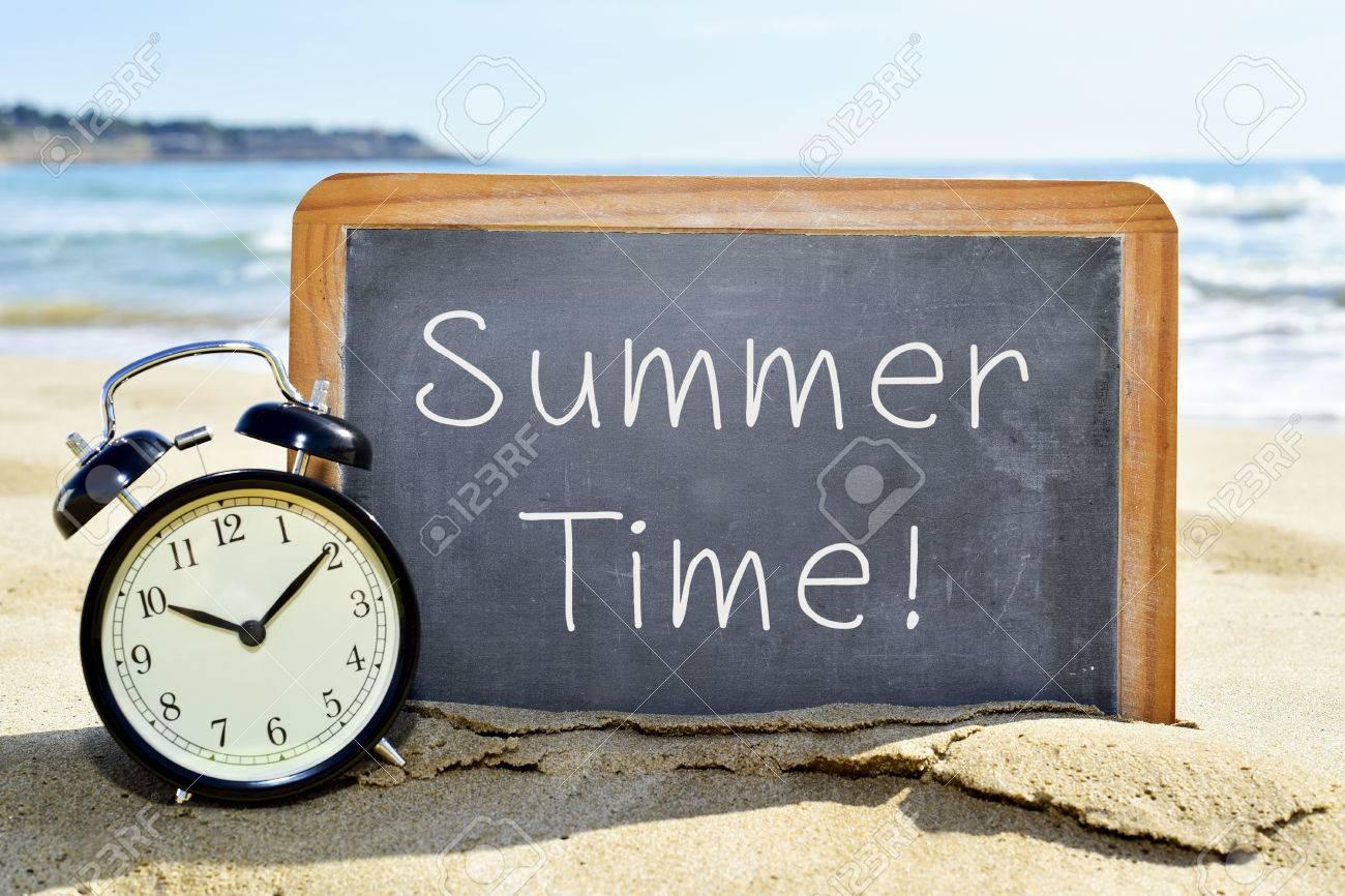 Un réveil et un tableau avec le texte l'heure d'été sur le sable d'une plage Banque d'images - 54039658
