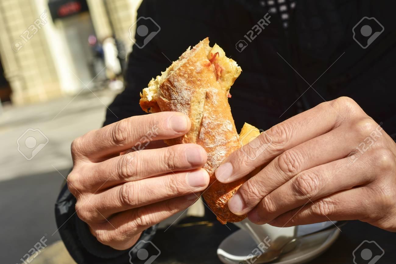 Joven Sentado En Una Mesa En La Terraza De Un Café Comiendo Un Bocadillo De Tortilla Española