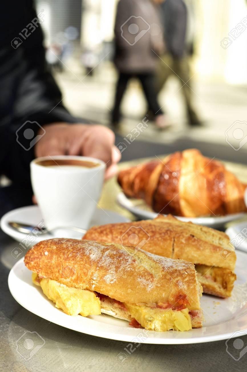 Hombre Sentado En Una Mesa En La Terraza De Un Café Puestas Para El Desayuno Con Algunas Tazas De Café Un Cruasán Y Un Bocadillo De Tortilla