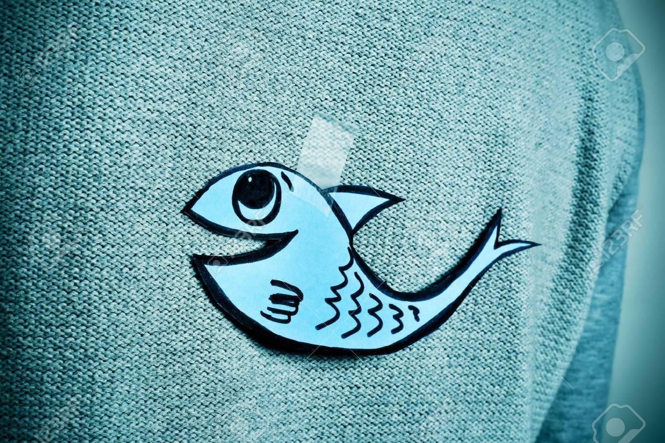 gros plan d'un jeune homme avec un poisson de papier attaché avec du ruban adhésif sur le dos, avec une légère vignette ajouté Banque d'images - 54039153
