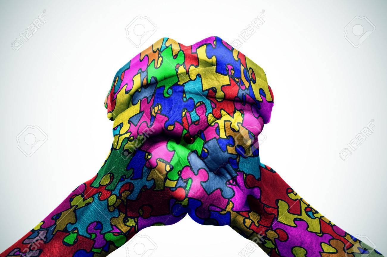 les mains de l'homme mis en place modelés avec de nombreuses pièces de puzzle de différentes couleurs, symbole de la sensibilisation à l'autisme, avec une légère vignette ajoutée Banque d'images - 54039116