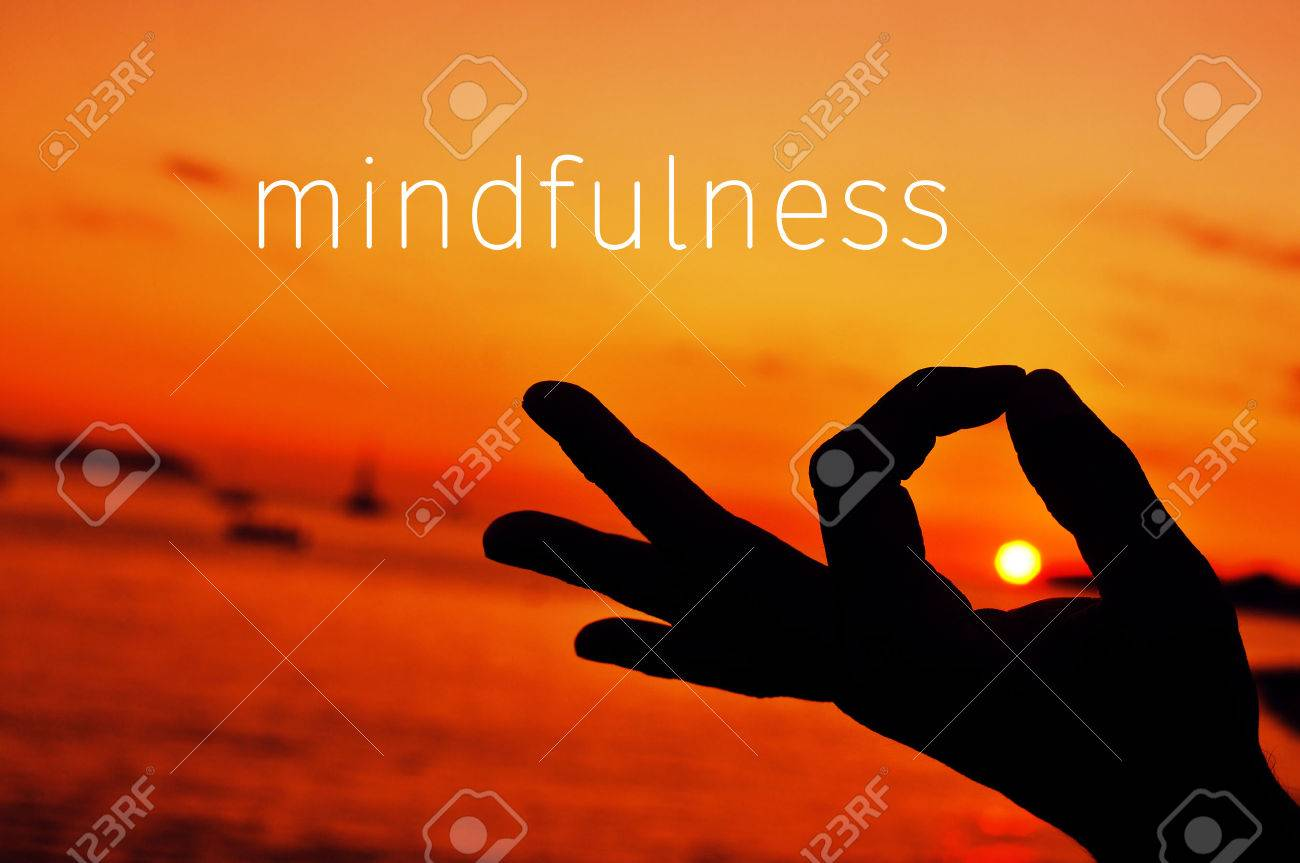 the text mindfulness and a closeup of a young man meditating with his hand in gyan mudra at sunset Banque d'images - 57434745