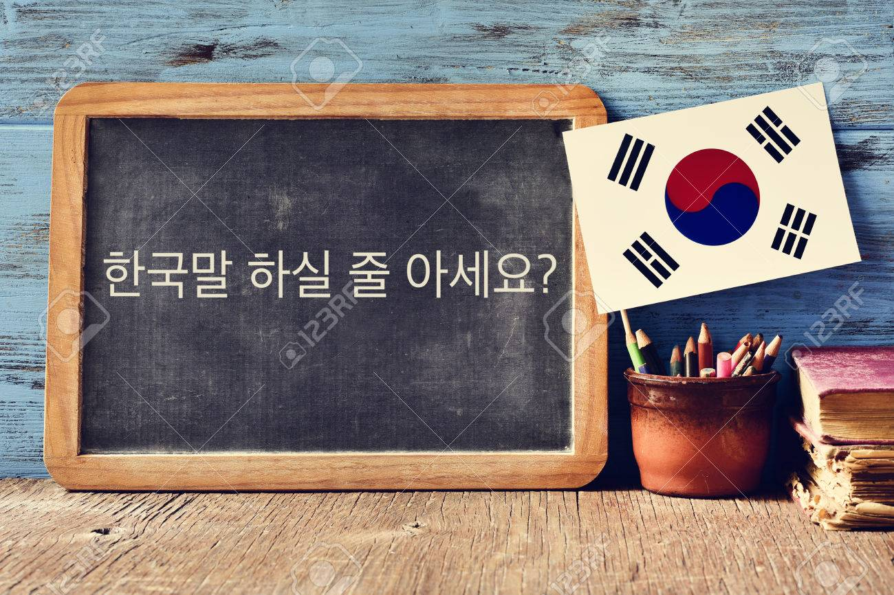a chalkboard with the question do you speak Korean? written in Korean, a pot with pencils, some books and the flag of South Korea, on a wooden desk - 69205890