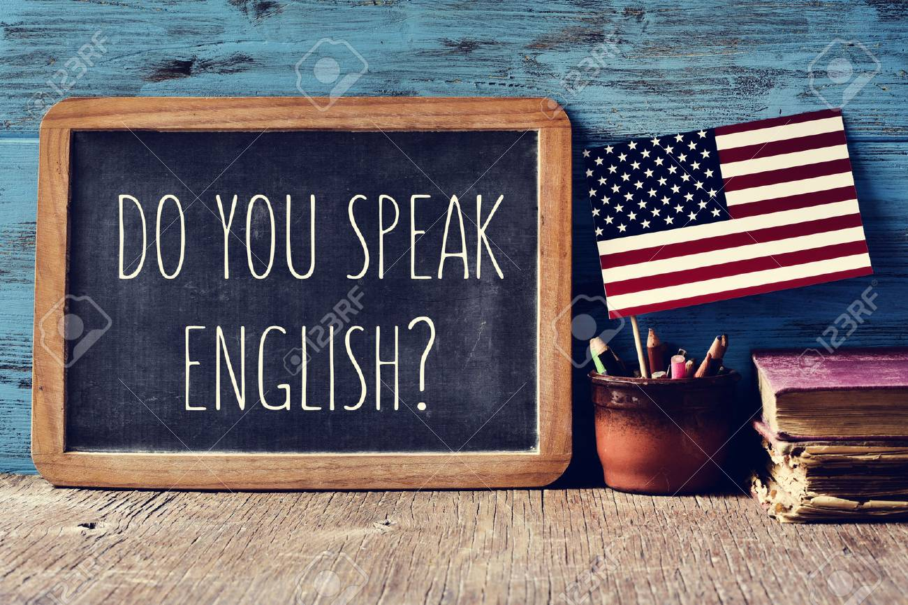 a chalkboard with the question do you speak English? written in it, a pot with pencils and the flag of the United States, on a wooden desk - 63892262
