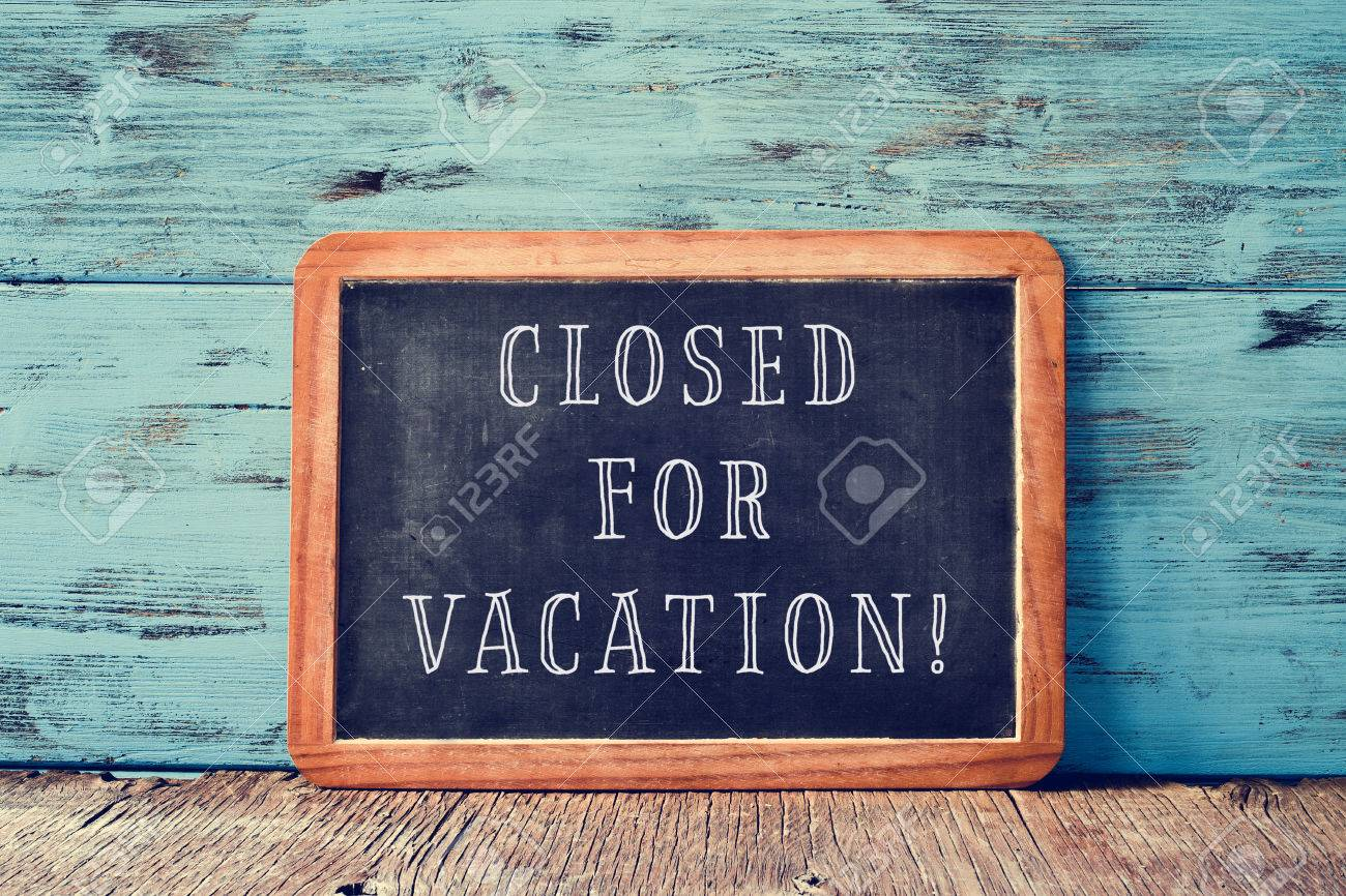 a wooden-framed chalkboard with the text closed for vacation written in it, on a rustic wooden surface, against a blue wooden background - 63160011