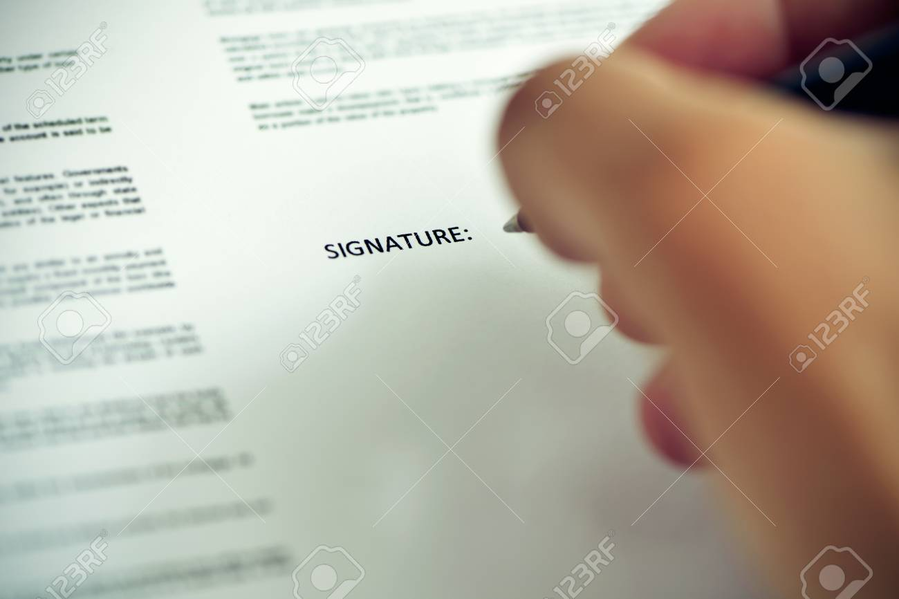 closeup of a young caucasian man about to sign a document with a pen under the word signature - 63701102