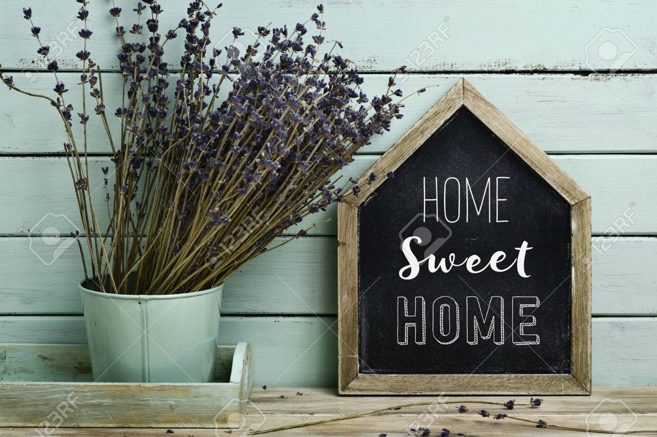 closeup of a house-shaped chalkboard with the text home sweet home written in it and a bunch of lavender flowers in a flower pot, against a rustic pale blue background Banque d'images - 63892578