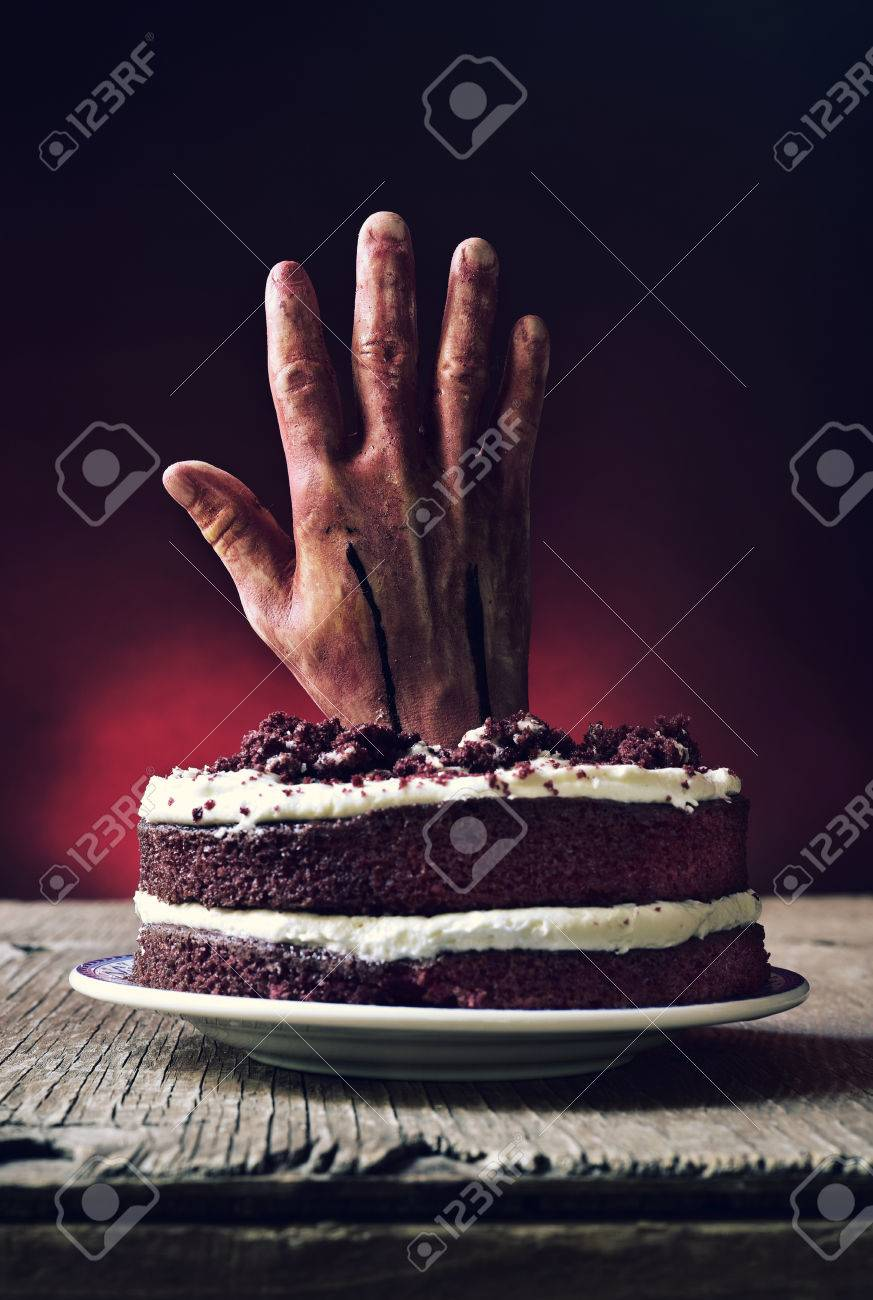 A Red Velvet Cake Topped With Bloody Hand In Scary Scene For Halloween