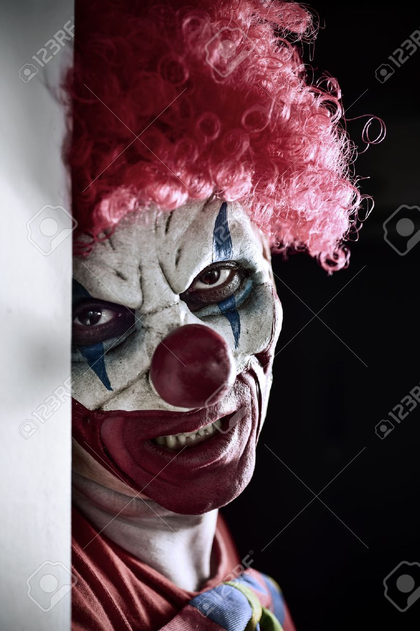 portrait of a scary evil clown against a dark background - 63769819