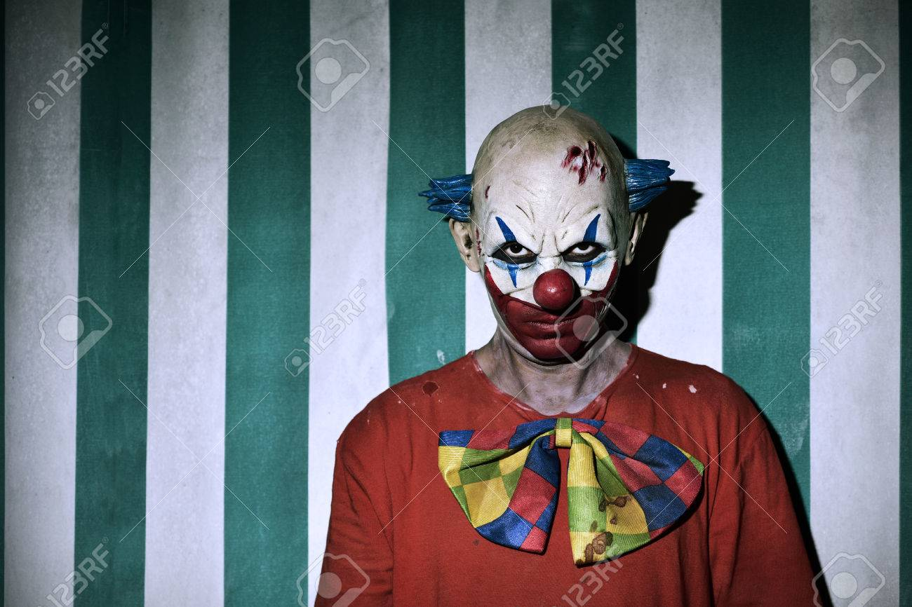 closeup of a scary evil clown wearing a dirty costume, with the circus tent in the background - 66157803