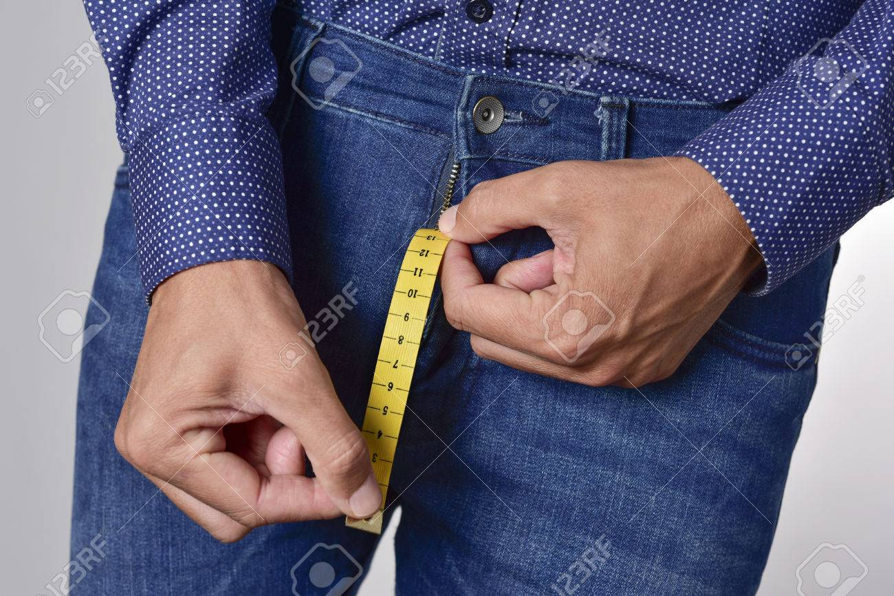 closeup of a young man holding a piece of measuring tape that is popping up from the fly of his jeans, depicting the normal range of the penis - 66158131