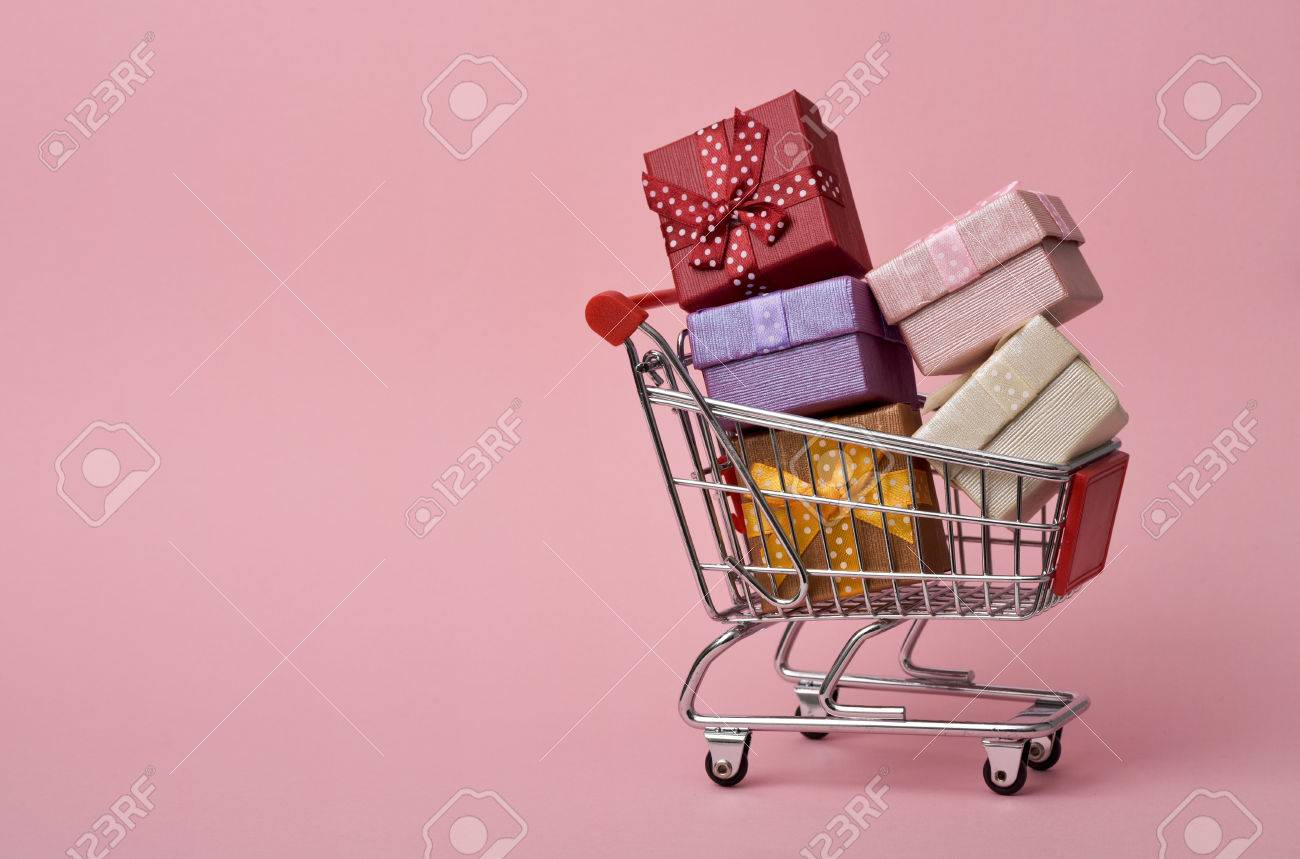 a shopping cart full of gifts of different colors on a pink background, with a negative space - 67764780