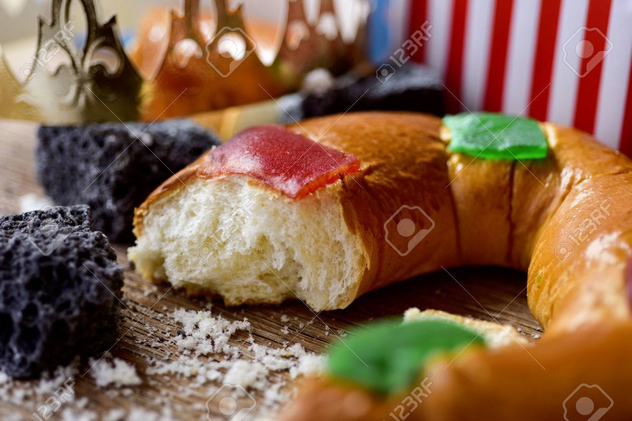 closeup of a roscon de reyes, the traditional spanish three kings cake eaten on epiphany day, and some pieces of candy coal on a rustic wooden table - 67701918