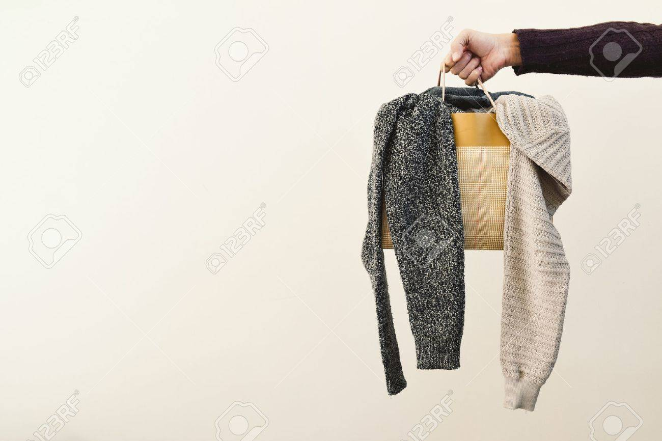 closeup of the hand of a young caucasian man holding a paper shopping bag full of clothes and a negative space to the left - 69227808