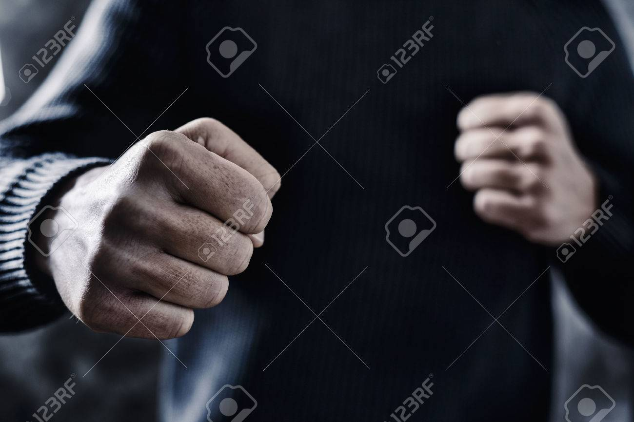 closeup of a young caucasian man in casual wear with a threatening gesture, ready to punch or fight with his fists - 70153463