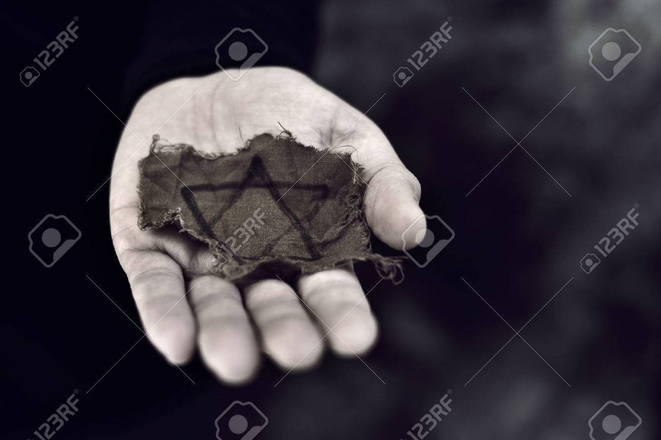 closeup of a ragged Jewish badge in the palm of a young man - 70331649