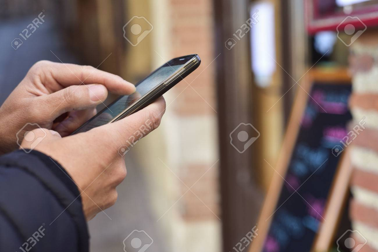 closeup of a young caucasian man using a smartphone in the street, in front of a restaurant - 70616757