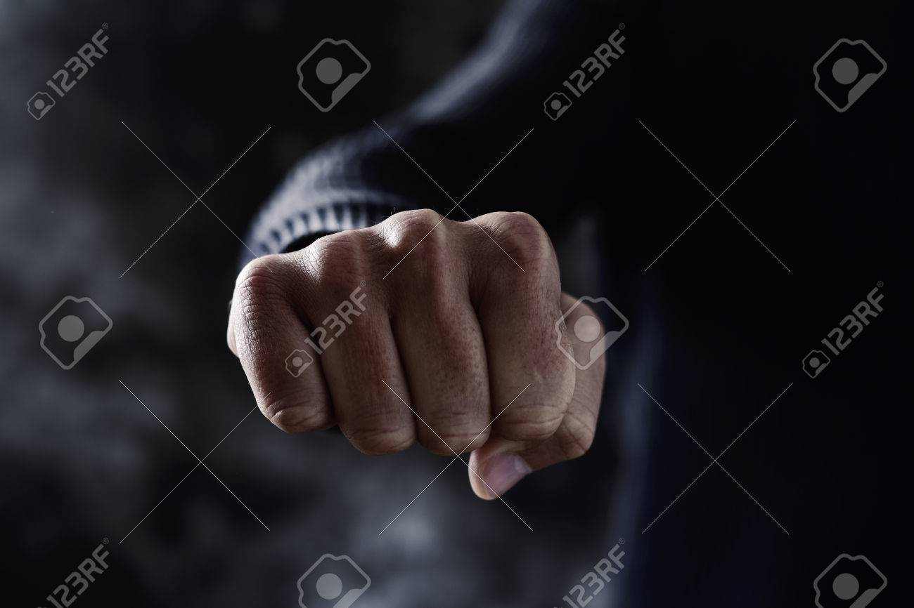 closeup of a young caucasian man in casual wear with a threatening gesture, with his fist clenched and pointing to the observer - 70656234