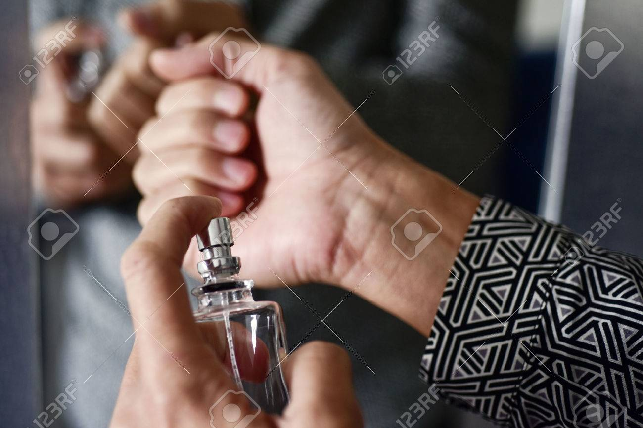 closeup of a young caucasian man spraying perfume on his wrists - 70949888